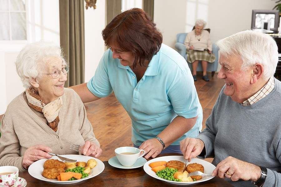 Senior-Couple-Being-Served-Meal