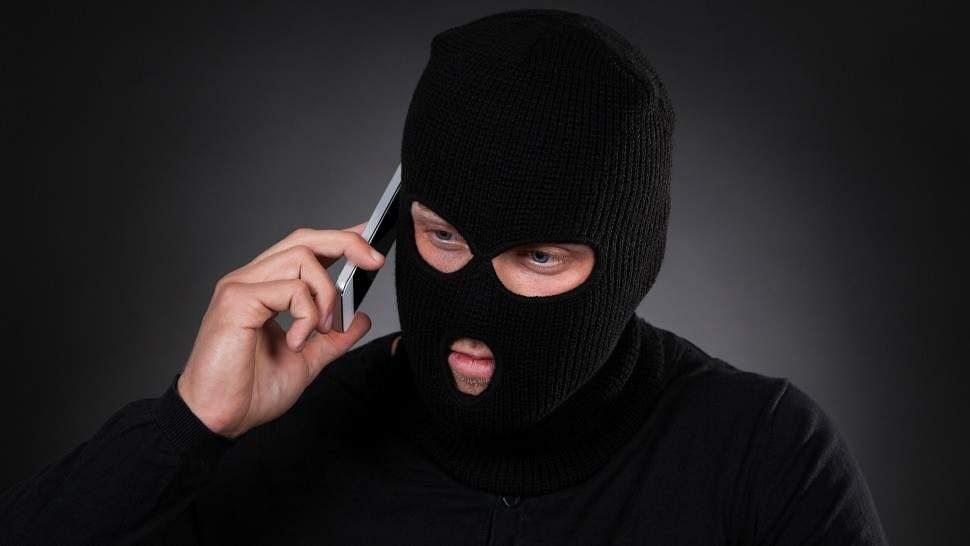 masked-robber-on-phone