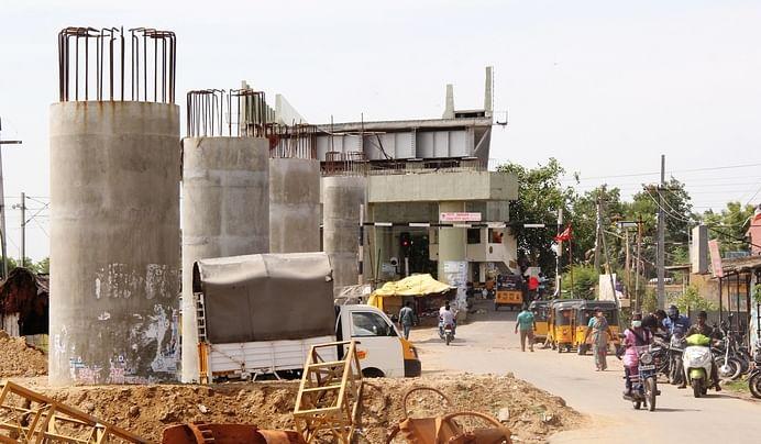 புட்லூா் ரயில் நிலையப் பகுதியில் மேம்பாலத்துக்காக அமைக்கப்பட்டுள்ள தூண்கள்.